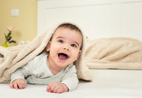 Baby lachend onder een deken
