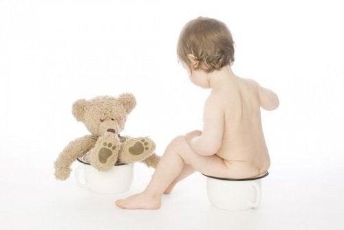 Kind op potje met teddybeer
