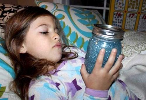 Meisje ontspant in bed met sensorische fles