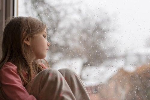 Verdrietig kind bij het raam