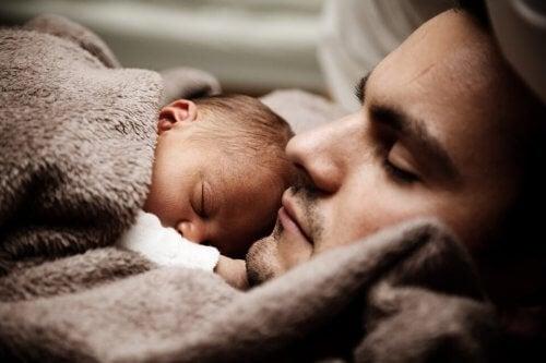 Baby in slaap op de borst van papa