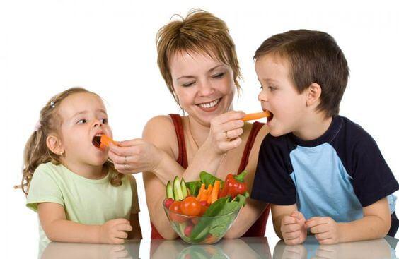 Moeder voert worteltjes aan haar kinderen
