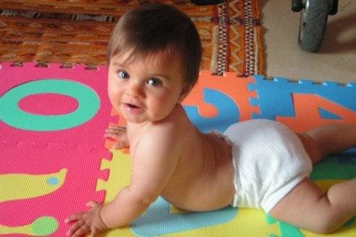 Baby in luier op speelmat