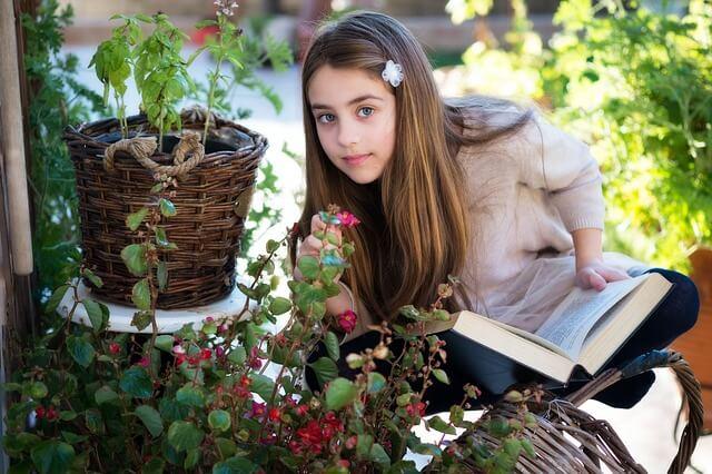 Meisje leest boek in de tuin