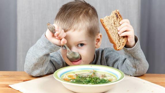 Jongen eet brood en soep