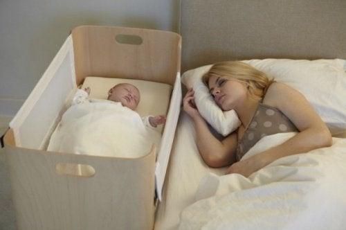 Moeder in bed naast baby in wieg