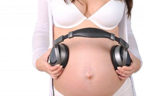 Zwangere buik met koptelefoon