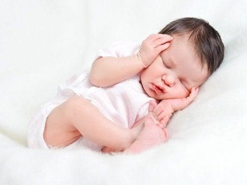 Slapende baby met handjes op hoofd