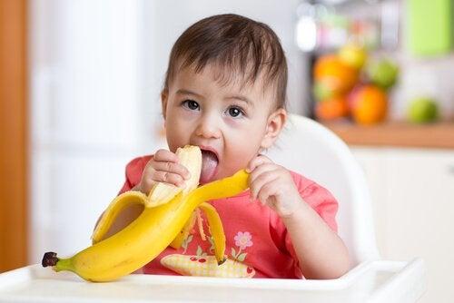 Baby eet banaan
