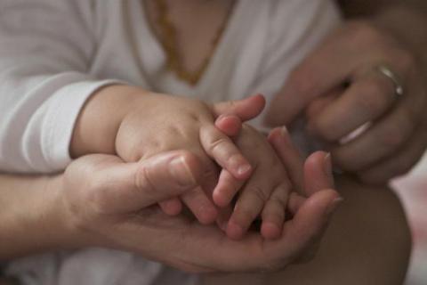 Handen van kind in die van een volwassene