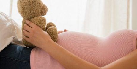 Knuffelbeer op de buik van een zwangere vrouw