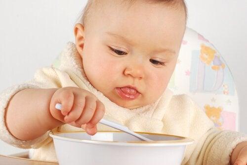 Baby eet met een lepel