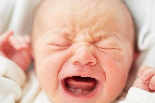 Baby huilt met gesloten ogen en open mond