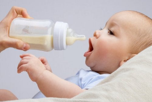 Baby wacht met open mond op fles