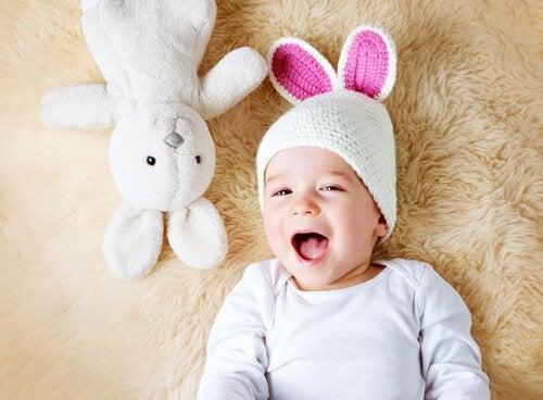 Baby en konijn liggen op een kleed
