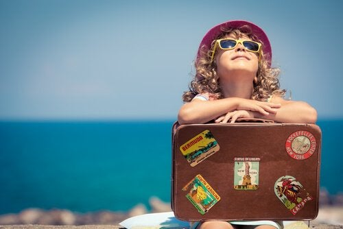 Kind met koffer aan zee