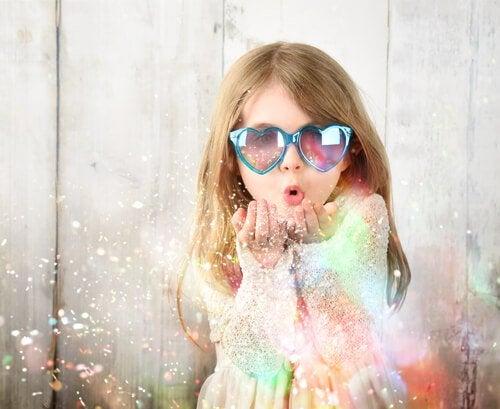 Meisje met zonnebril blaast magie