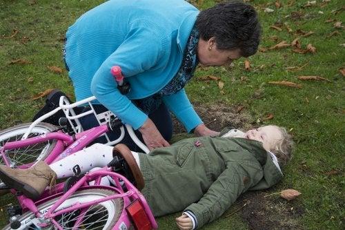 Meisje ligt op de grond onder fiets
