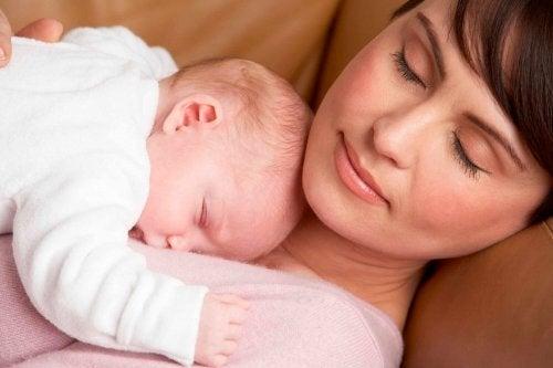 Moeder en baby doen dutje op de bank