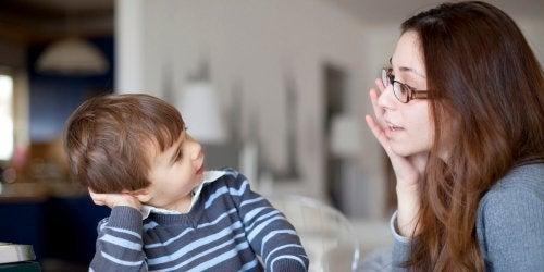 Moeder met bril praat met kind in gestreept shirt