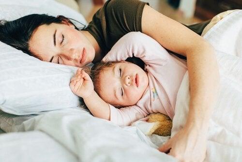Moeder houdt kind vast tijdens het slapen