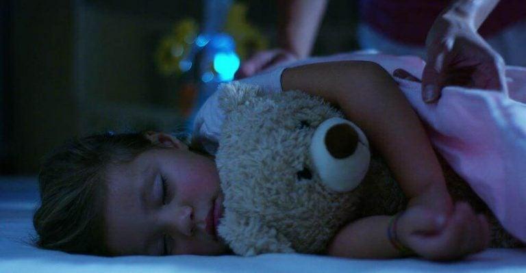 Meisje slaapt met knuffelbeer