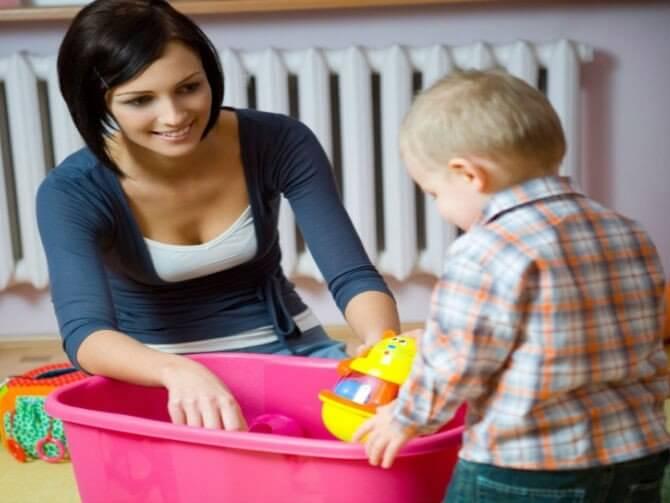 Kindje ruimt speelgoed op