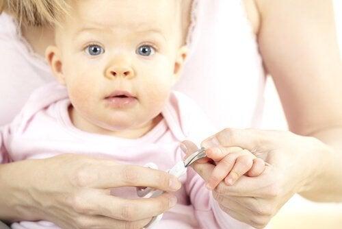 Vrouw knipt de nagels van je baby