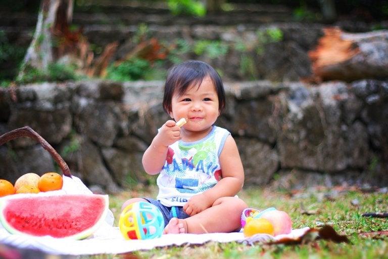 Baby eet fruit tijdens het spelen