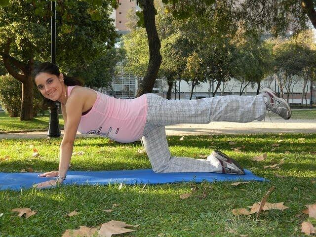 Vrouw buiten op een yogamat