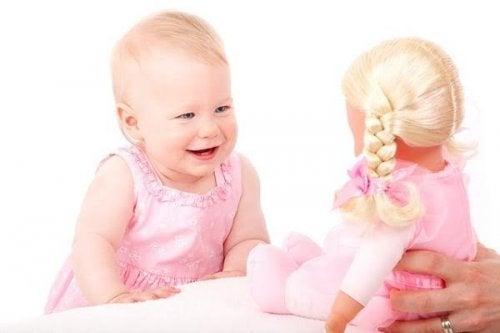 Leren lachen: baby met pop
