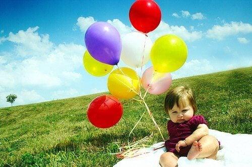 Baby met kleurrijke ballonnen