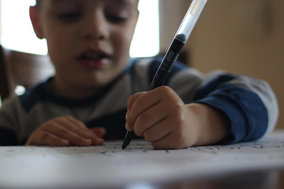 Kind schrijft met een stift