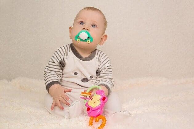 Baby met een speen en een speeltje
