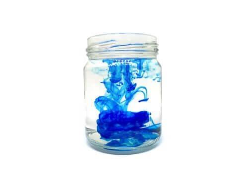 Glas met water en blauwe kleurstof