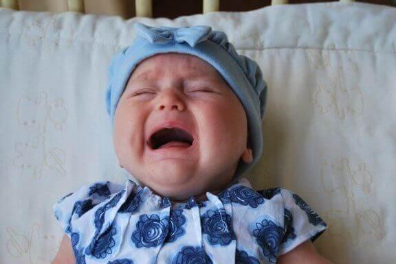 Baby met mutsje op die huilt