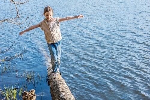 Meisje balanceert op een boomstam