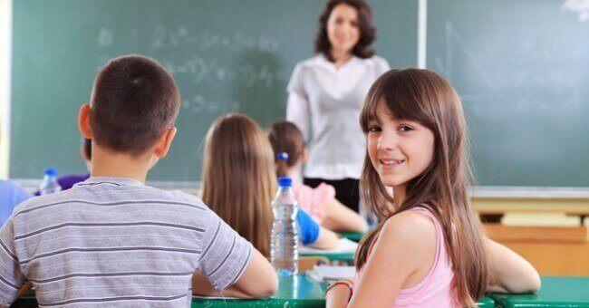 Meisje zit lachend in de klas