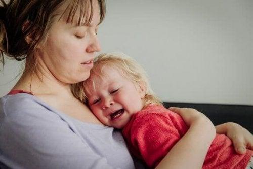 Een baby die huilt bij haar moeder