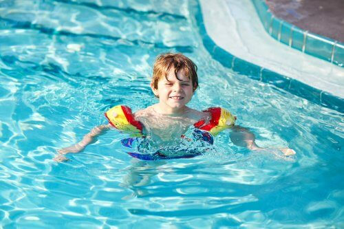 Jongen met zwembandjes in het zwembad