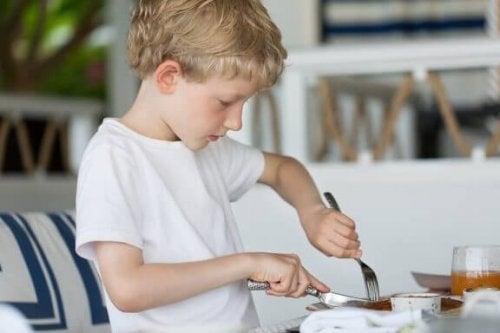 Een jongen snijdt zijn eten