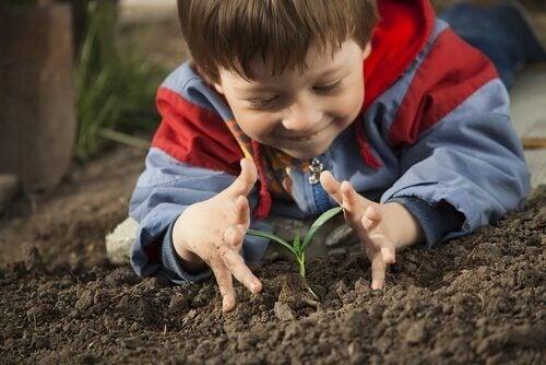 Kind bij een jong plantje heeft zo contact met de natuur