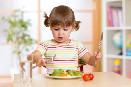 Klein kindje leert bestek gebruiken
