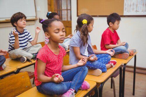 Kinderen mediteren op hun tafel in de klas