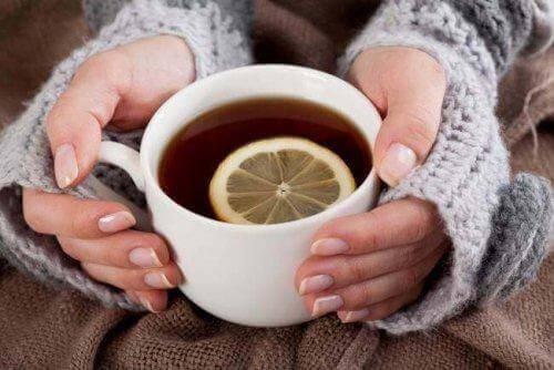 Handen van een vrouw met kopje citroenthee