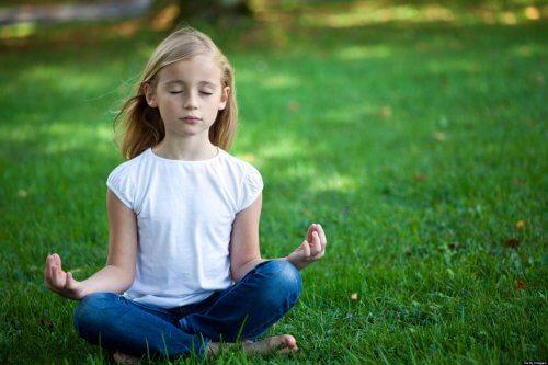 Meisje zit in het gras te mediteren