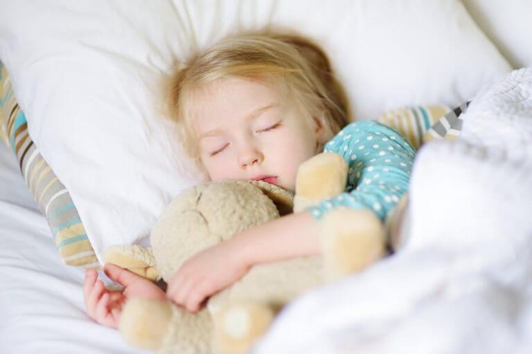 Kind slaapt met een beer