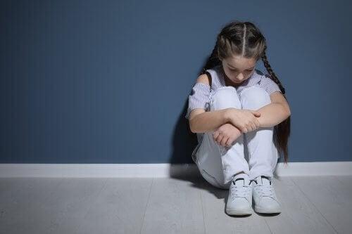 verdrietig meisje zit tegen een muur