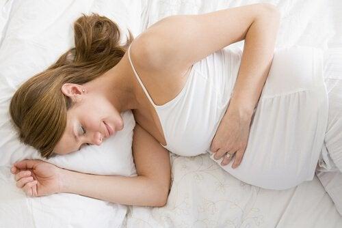 Zwangere vrouw ligt in bed te slapen