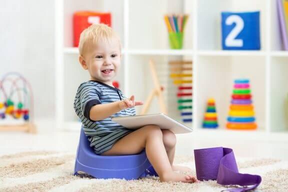 Jongetje zit op een potje te spelen